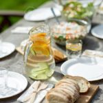 holidays, eating, mealtime and food concept - table with dinner at summer garden party
